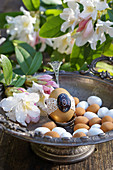 Egg with tip in a silver bowl with rhododendron flowers and marzipan eggs