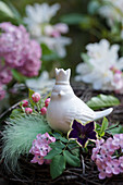Ceramic bird amongst lilac flowers, petunias, apple blossom and feather