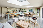 Country-house kitchen, dining and seating areas below skylights in open-plan interior