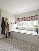Bathtub with white-tiled surround below window with patterned Roman blind