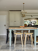 Various stools at breakfast bar in country-house kitchen