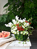 Summer flower arrangement of sweet peas, ivy, love-in-a-mist and jatropha in hollowed-out watermelon
