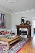 Opiumtisch im Wohnzimmer mit Stuckdecke und offenem Kamin