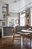 Designer chairs at dining table in front of country-house-style open-plan kitchen