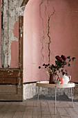 Kannen und Blumenstrauß auf rundem Tisch vor verfallener Wand
