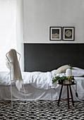 Bett vor weißer Wand mit schwarzem Sockel auf grafischem Teppich