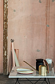 Golden watering can and ornaments in front of battered pink wall