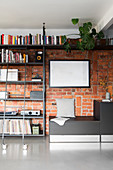 Bookcase with library ladder against brick wall in living room