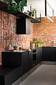 Black kitchen cabinets with plinth drawers against exposed brick walls