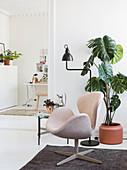 Designersessel und Monstera im Wohnzimmer im Skandinavischen Stil