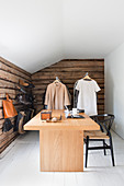 Modern desk in room with rustic wooden walls and clothes rails
