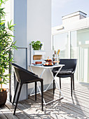 Plastic chairs at folding table on modern roof terrace