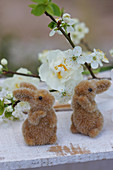Little Easter bunnies in front of narcissus and cherry blossom