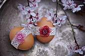 Easter eggs with lace ribbon and cherry plum blossom