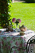 Romantically set tea table in summery château garden