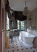 Bad im französischen Stil mit freistehender Badewanne, Kronleuchter und Vorhängen