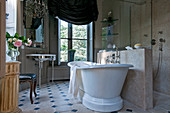 Free-standing bathtub next to half-height partition in French-style bathroom