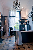 Free-standing bathtub, urn on plinth and chandelier in antique-style bathroom
