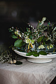 Arrangement of hellebores, gorse and twigs on cake stand