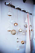 Festive arrangement of Christmas-tree baubles hung from coat rack