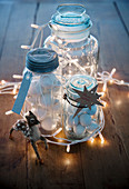 Festive arrangement of fairy lights and preserving jars filled with baubles