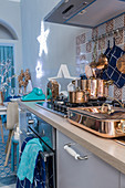 Copper pans on cooker in blue kitchen decorated for Christmas