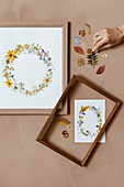 Hand legt Kranz aus gepressten Blumen in einen Bilderrahmen
