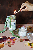 Lighting handmade scented candles with flowers in jars