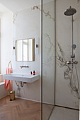 Walk-in shower in elegant bathroom with marble wall and parquet floor