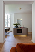 Open doorway leading into open-plan kitchen with island counter and dining table