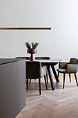 Upholstered chairs around modern dining table in puristic kitchen-dining room
