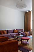 Orange armchairs and purple sofa in living room