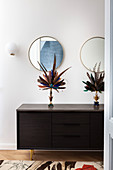 Decorative feather fans on black sideboard in hallway