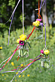 Flowers in screw top jars suspended from ribbons
