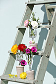 Flowers in vases made from wine glasses with concrete bases on stepladder
