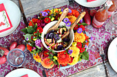 Colourful potato salad in wreath of flowers on set table