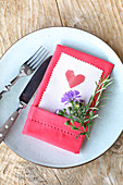 Heart printed on paper with pinked edge tucked into linen napkin