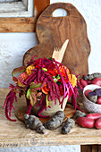 Colourful potatoes and late-summer bouquet with wooden cutlery