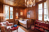 Old bed in classic wood-panelled child's bedroom