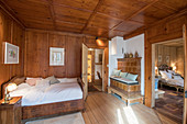 Traditional bedroom with wood panelling and tiled stove