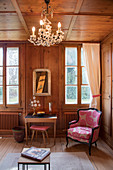 Pink-patterned armchair in traditional wood-panelled parlour