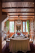Festively set table in wood-panelled dining room