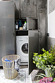 Washing machine and accessories stored in metal cupboard on balcony