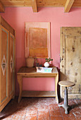 Farmhouse cupboard, writing desk and stool in corner of rustic room