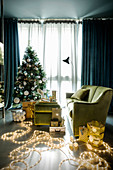 Green living room festively decorated with fairy lights and Christmas tree