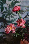 Pink peonies in front of wallpaper with leaf motifs