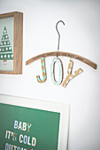Christmas decorations: Two collages and letters spelling 'Joy' hung from wooden coat hanger
