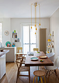 Dining table with wooden top on plexiglas base in bright, white kitchen with yellow accents