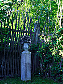 Urn on top of granite pillar in front of rustic fence made from branches