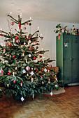 Klassischer Weihnachtsbaum in Rot und Weiß neben einem Spind